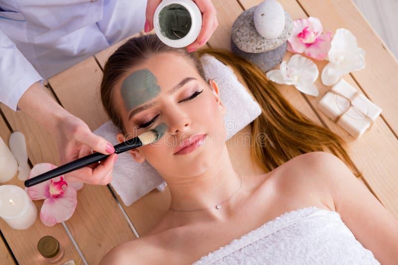 De jonge vrouw in het concept van de kuuroordgezondheid met gezichtsmasker stock afbeelding