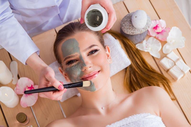 De jonge vrouw in het concept van de kuuroordgezondheid met gezichtsmasker royalty-vrije stock fotografie