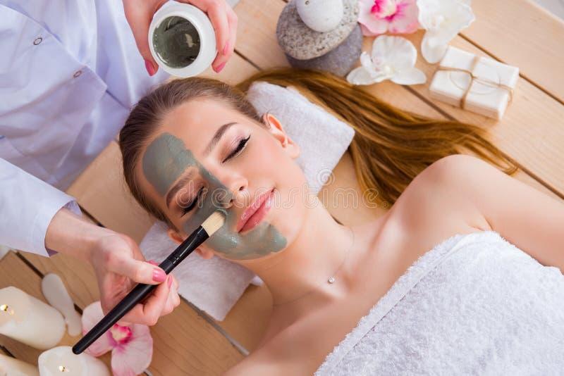 De jonge vrouw in het concept van de kuuroordgezondheid met gezichtsmasker stock fotografie