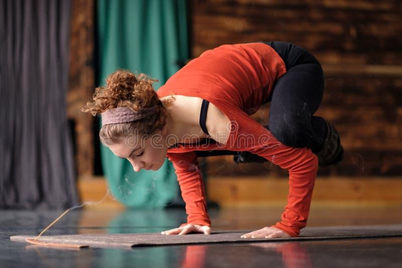 De jonge vrouw het praktizeren yoga, die Kraanoefening, Bakasana doen stelt, het uitwerken stock foto