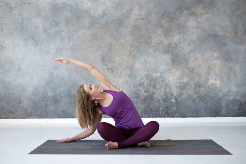 De jonge vrouw het praktizeren yoga, die in Sukhasana zitten stelt, zijkrommingsoefening royalty-vrije stock fotografie