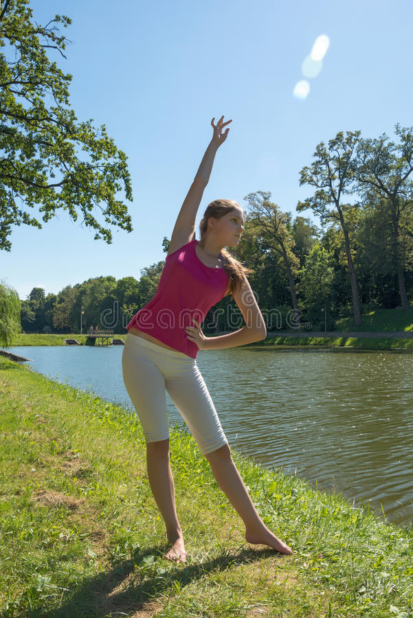 De jonge vrouw het praktizeren yoga door het meer royalty-vrije stock afbeeldingen