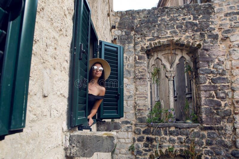 De jonge vrouw in hoed en zonnebril kijkt uit van het venster royalty-vrije stock afbeeldingen