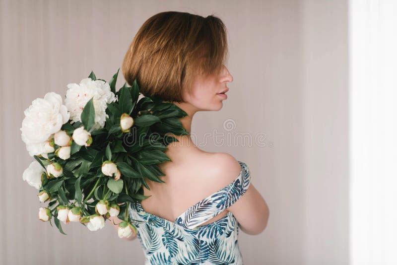 De jonge vrouw in de holdingsboeket van de fashonkleding van mooie witte pioenen bloeit achter haar achterst Valentine ` s Intern royalty-vrije stock afbeeldingen