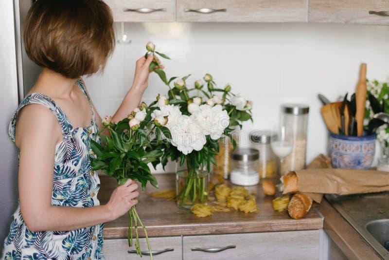 De jonge vrouw in de holdingsboeket van de fashonkleding van mooie witte pioenen bloeit achter haar achterst Valentine ` s Intern royalty-vrije stock fotografie
