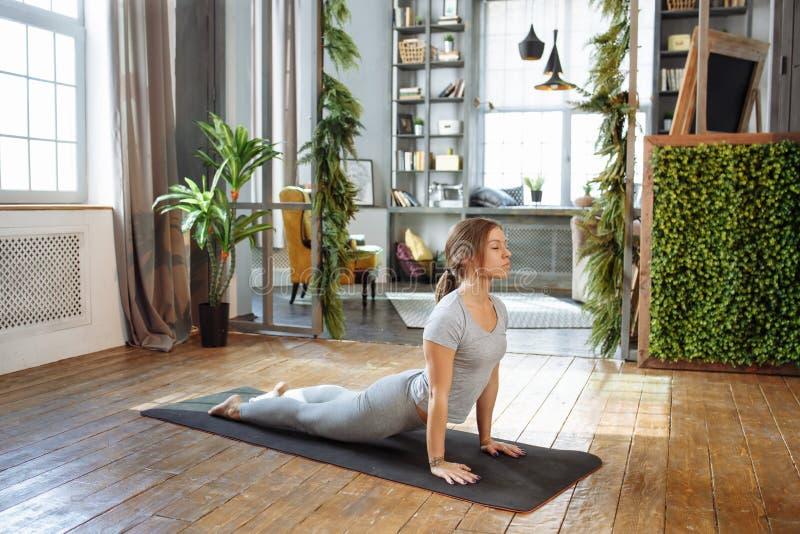 De jonge vrouw in homeware het praktizeren saldoyoga stelt op tapijt in haar slaapkamer op z'n gemak royalty-vrije stock afbeeldingen