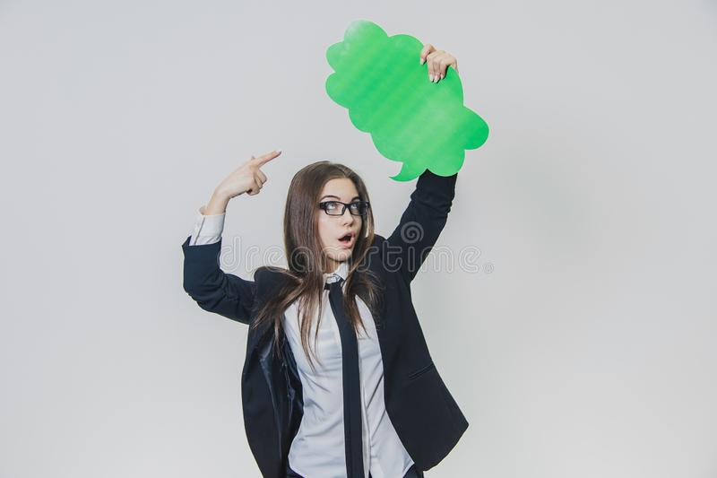 De jonge vrouw houdt een groene toespraakbel over zich, die, met één hand, op het wit wordt wolk-gevormd stock foto