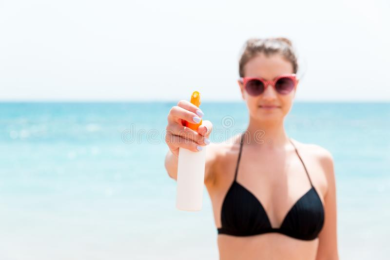 De jonge vrouw houdt een nevel van zonroom voor lichaam bij de camera bij het strand royalty-vrije stock afbeelding