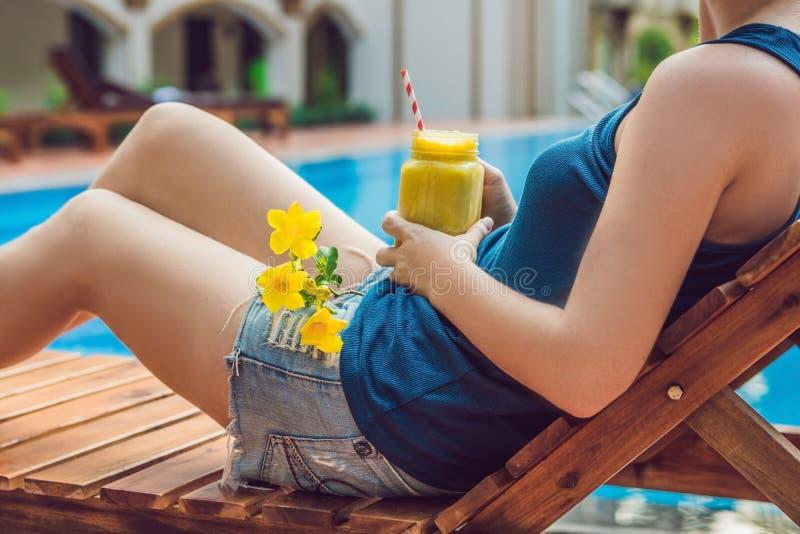 De jonge vrouw houdt een smoothie van mango op de achtergrond van de pool Fruit smoothie - gezond het eten concept sluit royalty-vrije stock foto