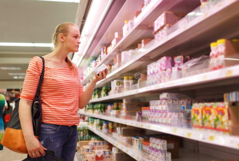 De jonge vrouw houdt een verpakkende babymelk stock afbeelding