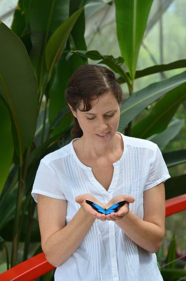 De jonge vrouw houdt in haar handen Ulysses Swallowtail stock afbeelding