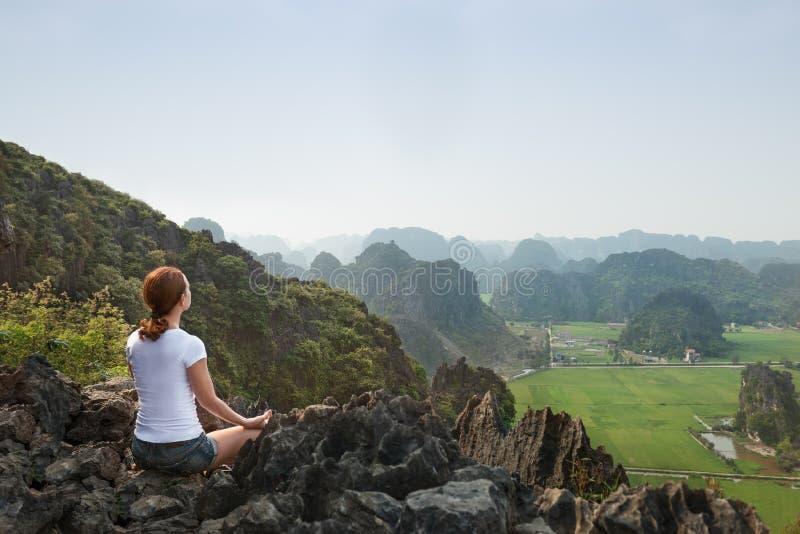 De jonge vrouw houdt kalm en mediteert terwijl het uitoefenen van yoga stock afbeeldingen