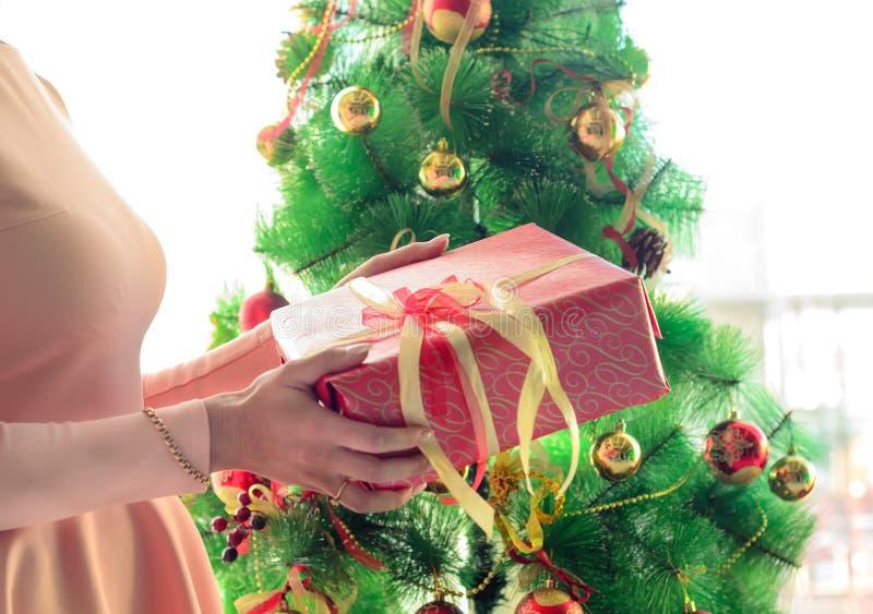 De jonge vrouw houdt Kerstmisgift dichtbij Kerstmisboom stock afbeeldingen