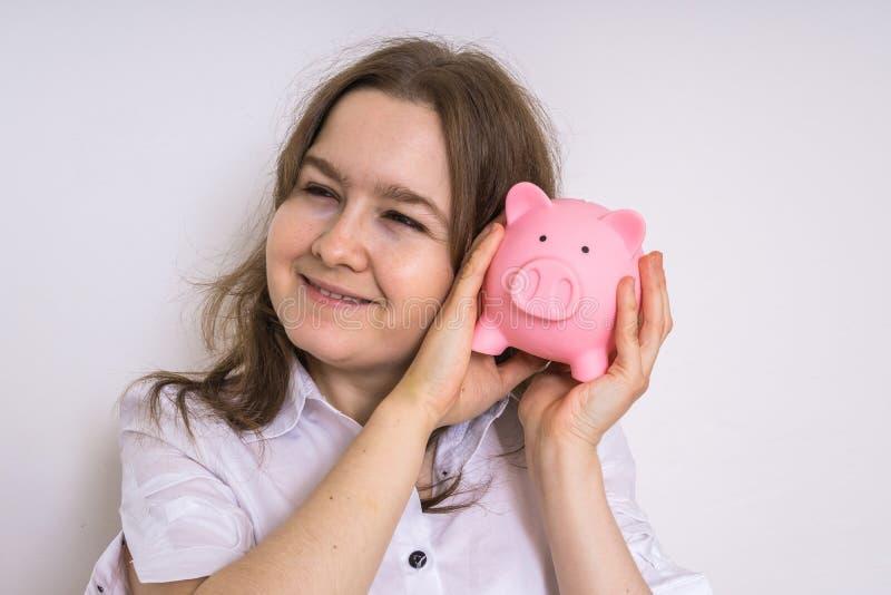 De jonge vrouw houdt piggy geldbank in handen en het dromen royalty-vrije stock foto