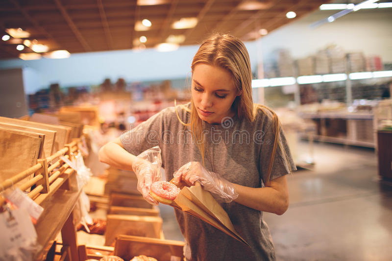De jonge vrouw kiest brood in de opslag royalty-vrije stock afbeelding