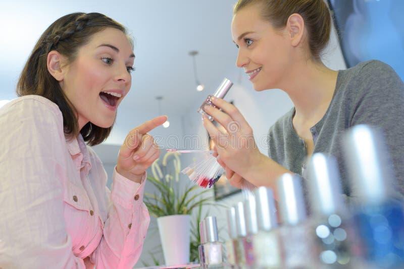 De jonge vrouw kiest parfum in winkel stock foto's