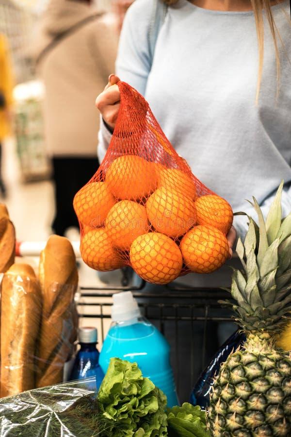 De jonge vrouw kiest verse sinaasappelen bij supermarkt stock afbeeldingen