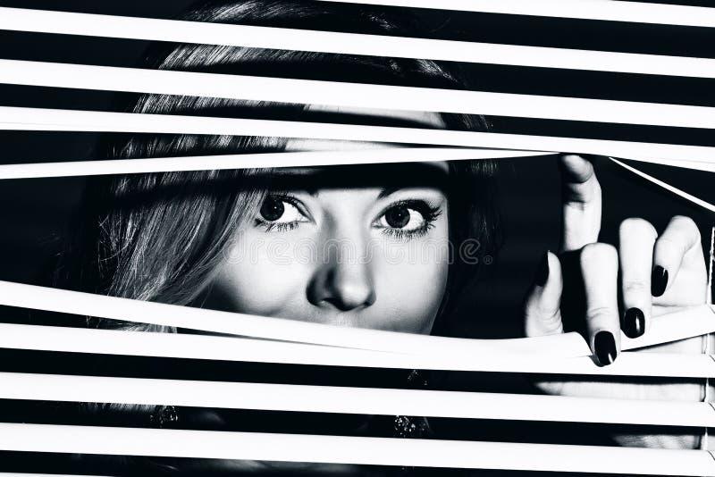 De jonge vrouw kijkt door de jaloezie royalty-vrije stock foto