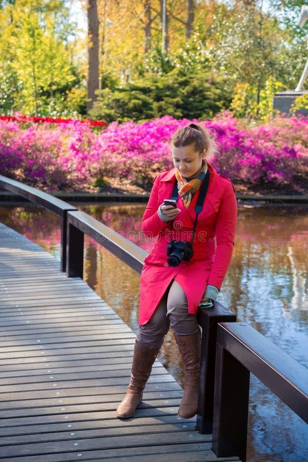 De jonge vrouw kijkt in een smartphone en glimlacht royalty-vrije stock foto's