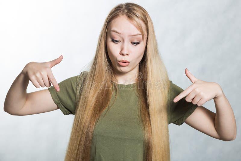 De jonge vrouw kijkt neer, uitdrukt surprisement, wijst op met wijsvingers bij vloer stock foto's