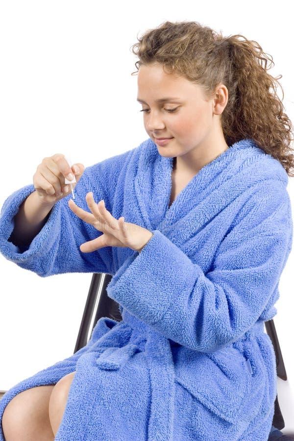De jonge vrouw kleedde blauwe badjas het schilderen spijkers royalty-vrije stock afbeelding