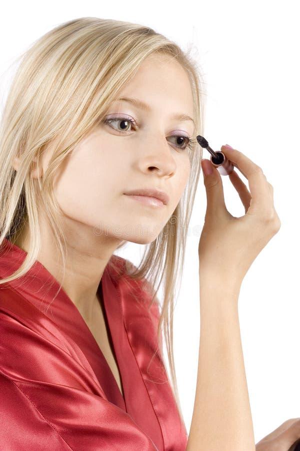 De jonge vrouw kleedde rode badjas zettend mascara stock afbeelding