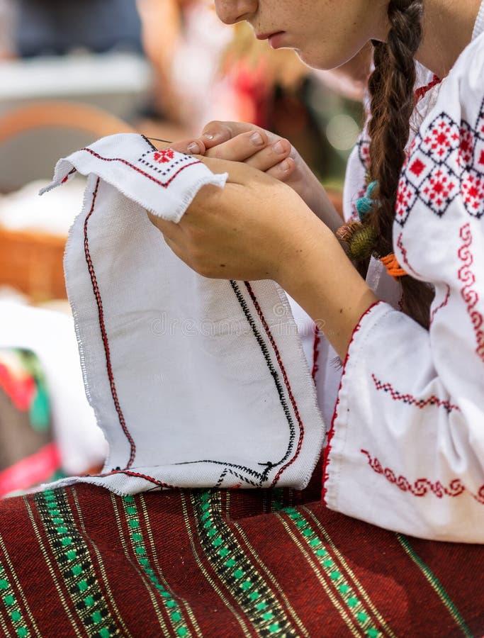 De jonge vrouw kleedde zich in een Roemeense volkshaven, die manueel werken bij stock fotografie