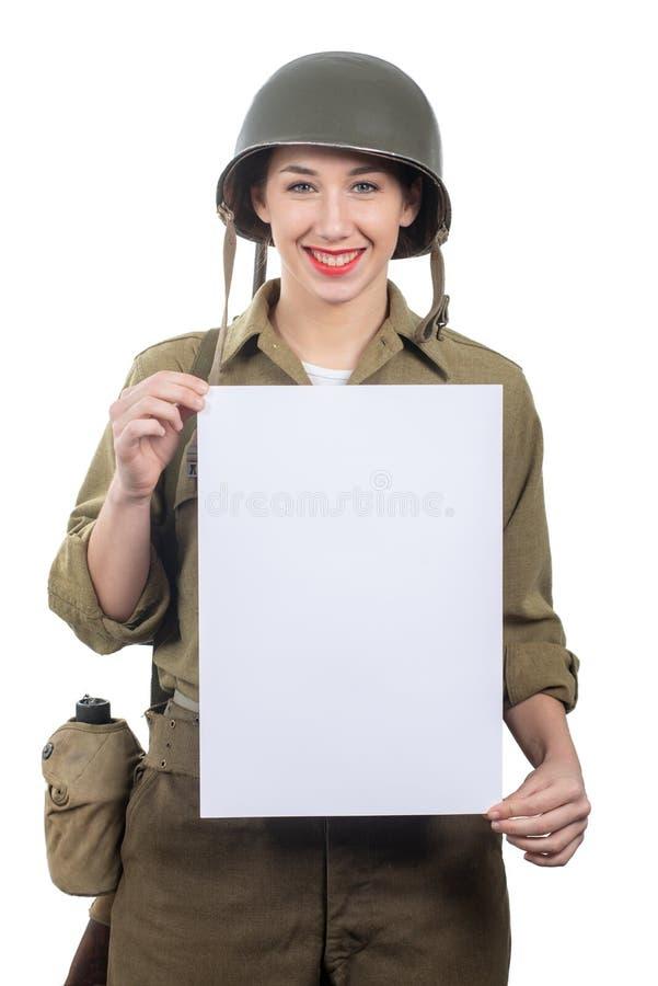 De jonge vrouw kleedde zich in het Amerikaanse militaire eenvormige tonende lege lege uithangbord van ww2 stock fotografie