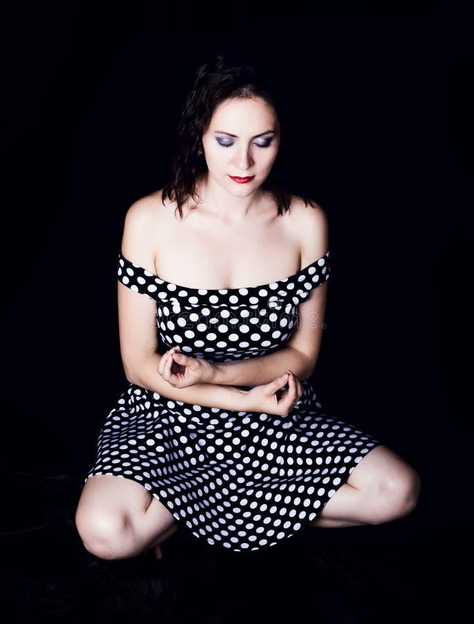 De jonge vrouw kleedde zich in korte kleding met naakte schouders, zittend in lotusbloemasana royalty-vrije stock foto