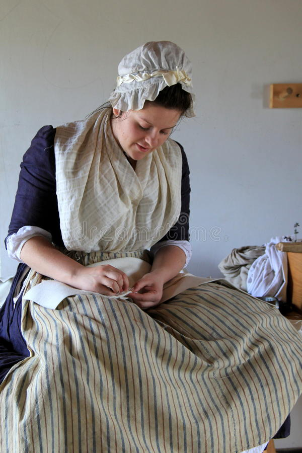 De jonge vrouw kleedde zich in periodekleding, die aan militair` s uniformen werken, Fort Ticonderoga, New York, 2016 stock afbeeldingen