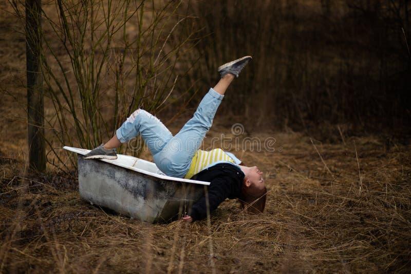De jonge vrouw in kleren neemt een leeg oud bad in het midden van een bos stock foto's