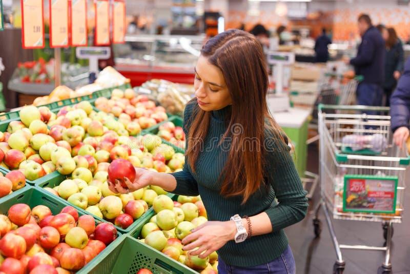 De jonge vrouw koopt appelen in de opslag van het landbouwbedrijfvoedsel stock afbeelding