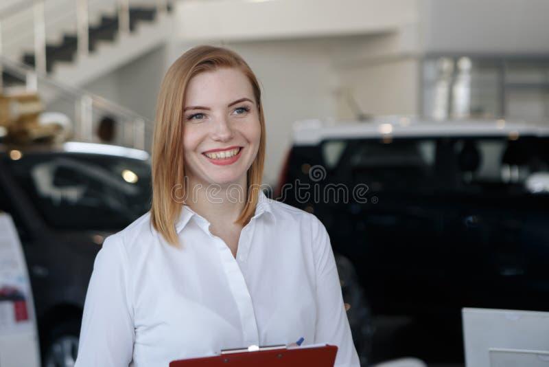 De jonge vrouw koopt een auto royalty-vrije stock afbeelding