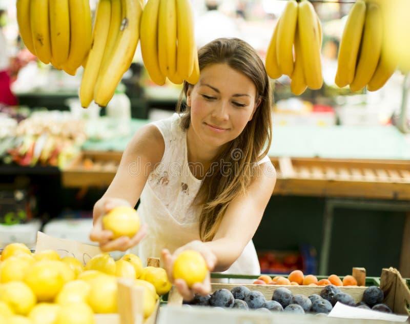 De jonge vrouw koopt fruit bij de markt stock foto