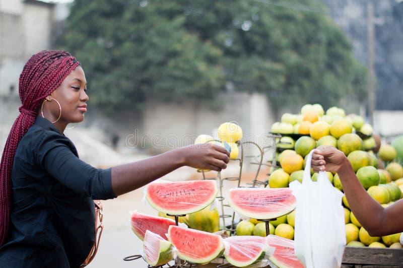 De jonge vrouw koopt fruit bij de straatmarkt stock fotografie