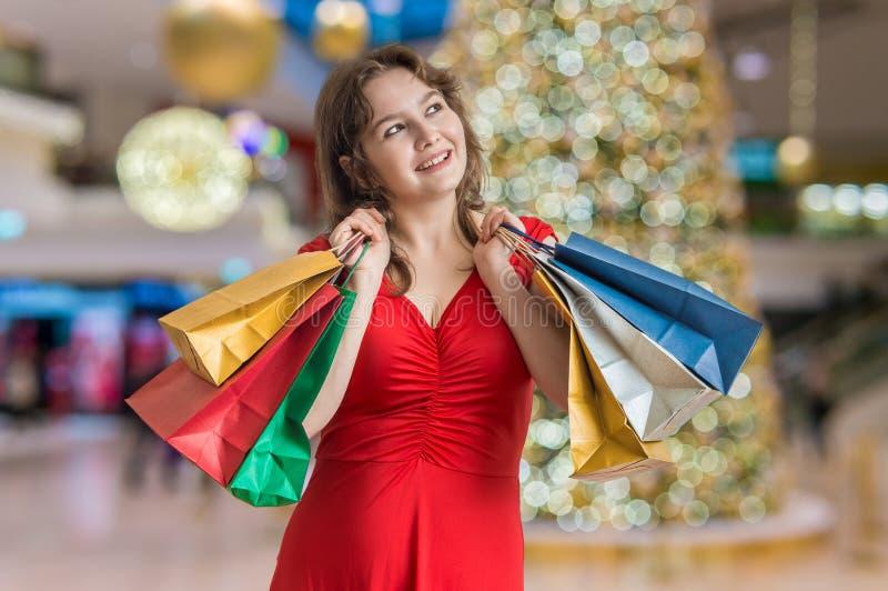 De jonge vrouw koopt giften voor Kerstmis en houdt vele colorfu royalty-vrije stock afbeelding