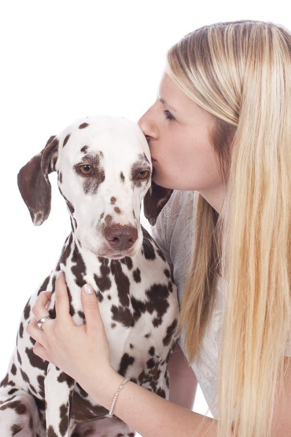 De jonge vrouw kust Dalmatische hond stock afbeelding