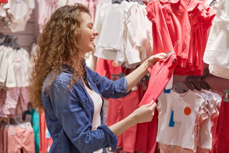De jonge vrouw kwam jonge geitjes in afdeling met kleren voor kleine kinderen, voelt gelukkig omdat zaag rode t-shirt voor kind e stock fotografie