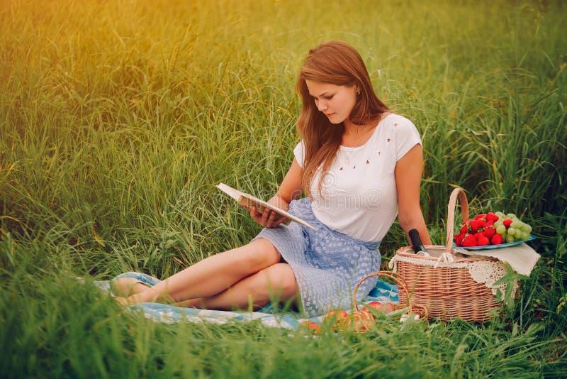 De jonge vrouw las in openlucht een boek Mand met erachter bessen royalty-vrije stock fotografie