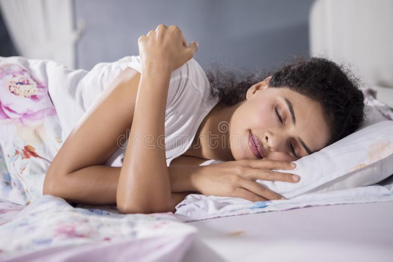 De jonge vrouw ligt in bed met gesloten ogen royalty-vrije stock afbeelding