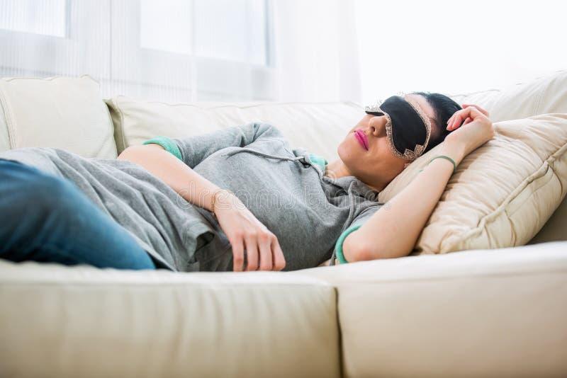 De jonge vrouw ligt met slaapmasker royalty-vrije stock foto