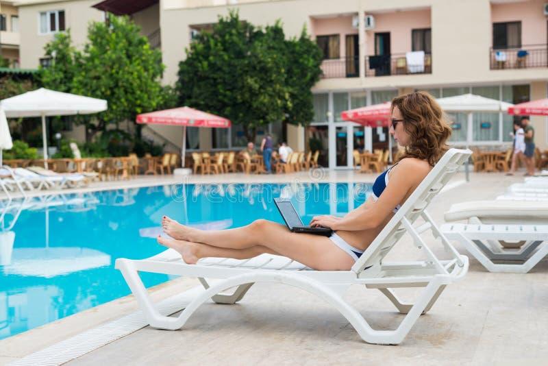De jonge vrouw ligt op een lanterfanter door de pool en werkt aan laptop Vrouwenwerkverslaafde die terwijl op vakantie, beschikba stock afbeeldingen