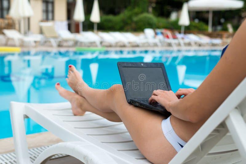 De jonge vrouw ligt op een lanterfanter en werkt aan laptop, laptop het schermclose-up Slanke vrouw die door de pool rusten stock afbeelding