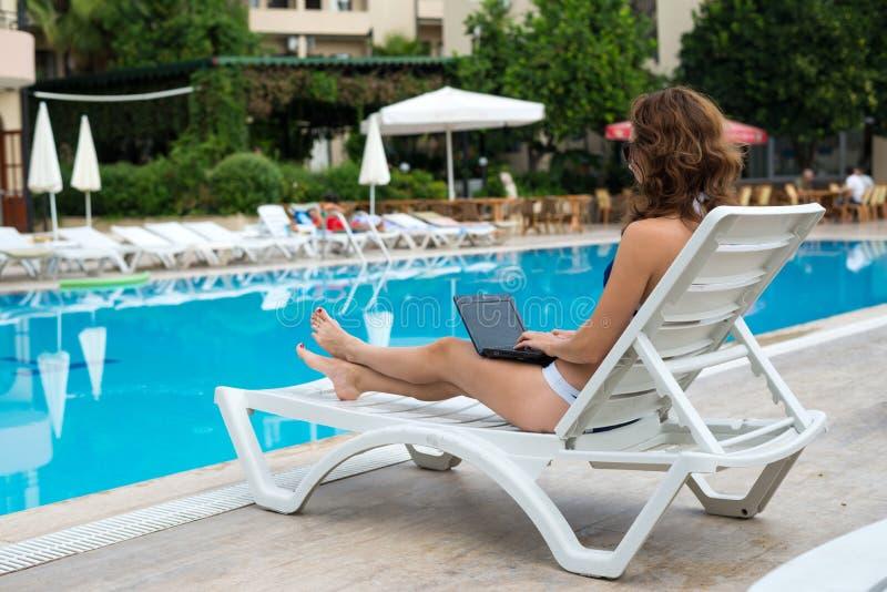 De jonge vrouw ligt op een lanterfanter en werkt aan laptop Slanke vrouw die door de pool rusten stock afbeelding