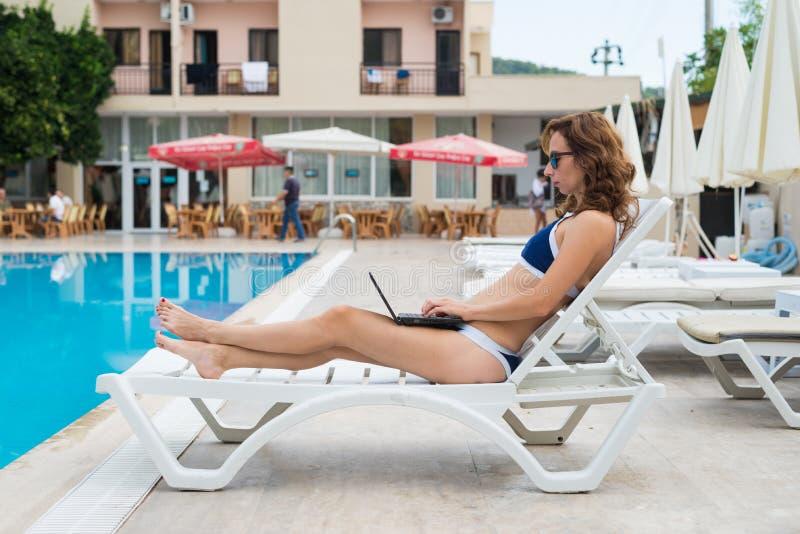 De jonge vrouw ligt op een lanterfanter en werkt aan laptop Slanke vrouw die door de pool rusten Het concept het verre werk, het  royalty-vrije stock afbeelding