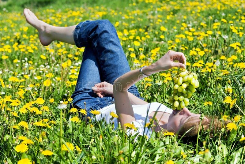 De jonge vrouw ligt op een weide stock foto