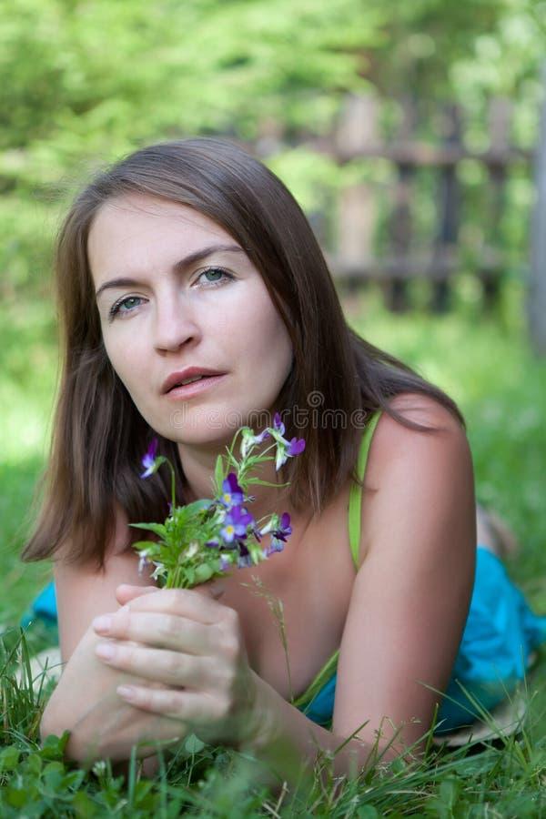 De jonge vrouw ligt op gras royalty-vrije stock fotografie