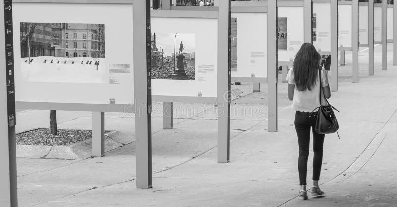 De jonge vrouw loopt voorbij een openluchtfototentoongesteld voorwerp stock afbeeldingen