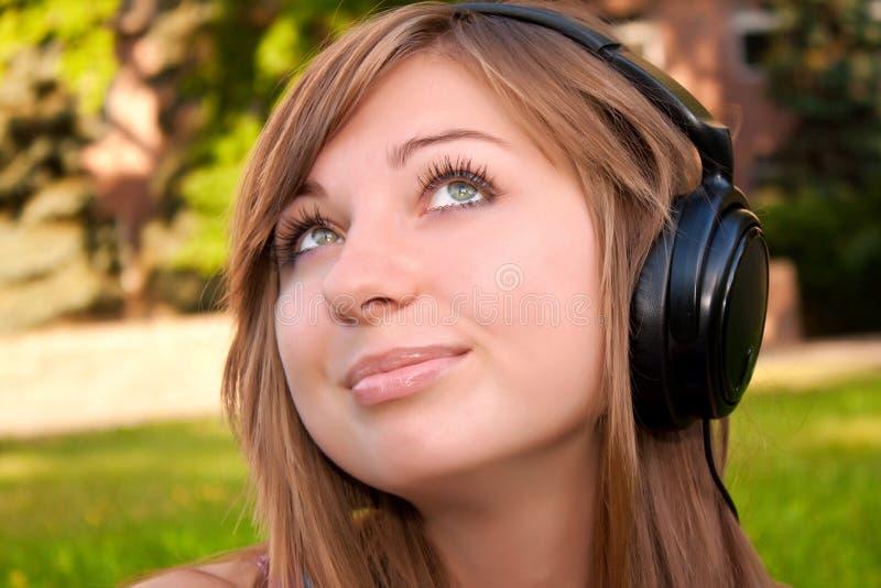 De jonge vrouw luistert aan de muziek stock fotografie