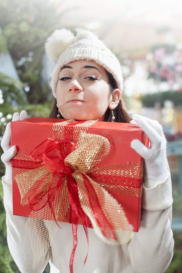 De jonge vrouw maakt een grappig gezicht en klemt haar gift dicht royalty-vrije stock fotografie